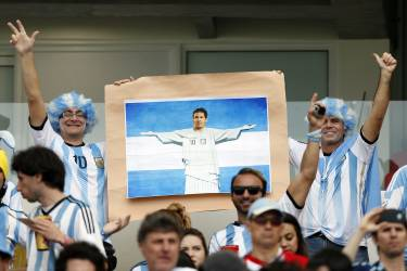 Argentina fan hold a picture of Lionel Messi as Christ the redeemer prior to the group F World Cup soccer match between Nigeria and Argentina at the Estadio Beira-Rio in Porto Alegre, Brazil, Wednesday, June 25, 2014. (AP Photo/Victor R. Caivano)