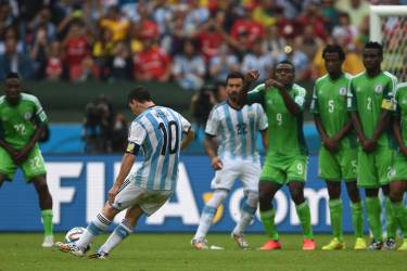 Argentina's forward Lionel Messi shoots to score his second goal, during a Group F football match between Nigeria and Argentina at the Beira-Rio Stadium in Porto Alegre during the 2014 FIFA World Cup on June 25, 2014.  AFP PHOTO / PEDRO UGARTE