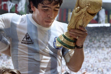 Argentina's forward Diego Maradona is carried on the shoulders of fans as he does a victory lap holding the FIFA World Cup after Argentina defeated West Germany 3-2 in the World Cup final on June 29, 1986 in Mexico City.