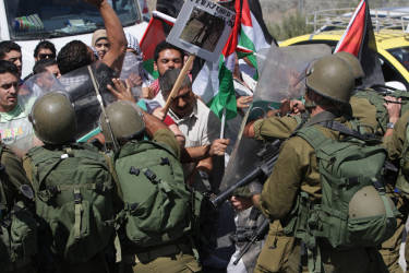 Palestinians confront Israeli soldiers during a demonstration against Israeli military action in Gaza, near the West Bank town of Nablus, Monday, July 14, 2014. Israel began its campaign against militants in the Hamas-controlled Gaza last Tuesday, saying it was responding to heavy rocket fire from the densely populated territory. The military says it has launched more than 1,300 airstrikes since then, while Palestinian militants have launched nearly 1,000 rockets at Israel. (AP Photo/Nasser Ishtayeh)