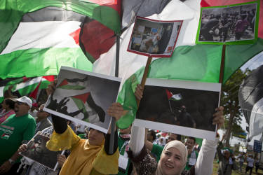 Members of the Palestinian community resident in Nicaragua, hold up Palestinian flags and photos, protesting Israeli air strikes on the Gaza strip, during a demonstration outside the U.N. headquarters in Managua, Nicaragua, Monday, July 14, 2014. (AP Photo/Esteban Felix)
