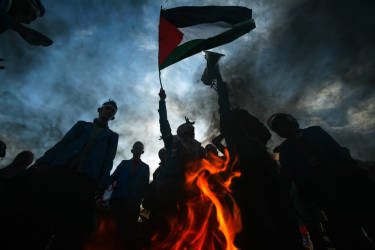 TOPSHOTSIndonesian demonstrators raise the Palestinian flag while they burn an Israeli and US flag during a demonstration in Banda Aceh, on Sumatra island on July 16, 2014, condemning Israel's offensive in Gaza. Israel urged 100,000 Gazans to flee their homes on July 16, but the warning was largely ignored despite an intensification of the military's nine-day campaign after Hamas snubbed a ceasefire effort. Indonesia with a population of about 220 million is the world's most populous Muslim-majority country.  AFP PHOTO / CHAIDEER MAHYUDDIN