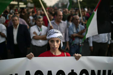 A protester holds a banner as she chants slogans against the Israeli air strikes on Gaza during a massive demonstration outside the Israeli embassy in Athens on July 17, 2014.   Israeli air strikes in Gaza killed four children on July 17, medics said, hours after a temporary humanitarian ceasefire ended.  Their deaths brought the toll in Gaza in a 10-day Israeli operation to stamp out militant rocket fire to 237, with at least 1,770 wounded. AFP PHOTO/ LOUISA GOULIAMAKI