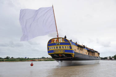 People sail on the Charente river on board the replica of the Hermione, the frigate on which La Fayette embarked in 1780, during its launching ceremony on July 6, 2012 in Rochefort, western France. Pulled by two tugboats, the hull of the frigate, with neither mast nor sail or rigging, will sail a few hours on the Charente before anchoring in front of the former royal rope factory to prepare a transatlantic crossing in 2015. AFP PHOTO / XAVIER LEOTY