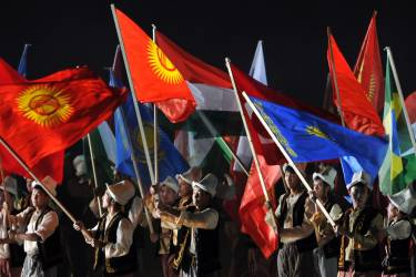 Participants wave flags of the countries competing in the first World Nomad Games during the opening ceremony at the hippodrome of Cholpon-Ata, some 270 kms outside the capital Bishkek, on September 9, 2014. Teams of Azerbaijan, Kazakhstan, Belarus, Mongolia and Tajikistan are taking part in the games. AFP PHOTO / VYACHESLAV OSELEDKO