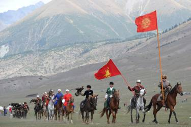 Riders carry flags during the first World Nomad Games in the Kyrchin (Semenovskoe) gorge, some 300 km from Bishkek on September 11, 2014 . Teams of Azerbaijan, Kazakhstan, Belarus, Mongolia and Tajikistan take part in the games. AFP PHOTO / VYACHESLAV OSELEDKO
