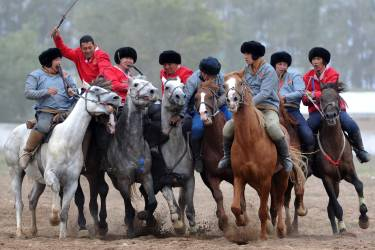 Kyrgyz (red) and Tajik (grey) riders play the traditional Central Asian sport Buzkashi also known as Kok-Boru or Oglak Tartis in the first World Nomad Games in Cholpon-Ata, some 270 km from Bishkek on September 11, 2014 . Mounted players compete for points by throwing a stuffed sheepskin into a well. Teams of Azerbaijan, Kazakhstan, Belarus, Mongolia and Tajikistan take part in the games. AFP PHOTO / VYACHESLAV OSELEDKO