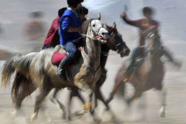 Kyrgyz (blue) and Turkish (red) riders play the traditional Central Asian sport Buzkashi also known as Kok-Boru or Oglak Tartis in the first World Nomad Games in Cholpon-Ata, some 270 km from Bishkek on September 12, 2014 . Mounted players compete for points by throwing a stuffed sheepskin into a well. Teams of Azerbaijan, Kazakhstan, Belarus, Mongolia and Tajikistan take part in the games. AFP PHOTO / VYACHESLAV OSELEDKO