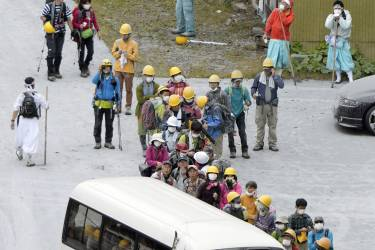 Climbers descended to a parking lot located halfway up Mt. Ontake line up to get on a bus after fleeing from the volcano eruption, in Kiso in Nagano Prefecture, central Japan, Saturday, Sept. 27, 2014. With a sound likened to thunder, the 3,067-meter (10,062-foot) mountain spewed large white plumes high into the sky, sending people fleeing, covering surrounding areas in ash and trapping more than 250 climbers. (AP Photo/Kyodo News) JAPAN OUT, MANDATORY CREDIT