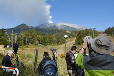 Photographers gather at the foot of the Mount Ontake in Nagano prefecture on September 28, 2014. The volcano erupted in central Japan on September 27, shooting ash and rocks into the air that reportedly left eight hikers injured and forced 150 people to shelter in cabins near the summit. The eruption of the 3,067-metre (10,121-foot) Mount Ontake happened around midday, the meteorological agency said.  AFP PHOTO / KAZUHIRO NOGI