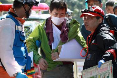 An injured climber, center, is helped by a firefighter, left, after descending Mount Ontake in Gero, Gifu prefecture, central Japan Sunday, Sept. 28, 2014. Mount Ontake in central Japan erupted shortly before noon Saturday, spewing large white plumes of gas and ash high into the sky and blanketing the surrounding area in ash. An estimated 40 people were stranded at mountain lodges overnight, many injured and unable or unwilling to risk descending 3,067-meter (10,062-foot) Mount Ontake on their own. (AP Photo/Kyodo News) JAPAN OUT, MANDATORY CREDIT
