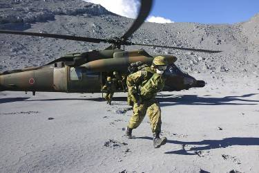 Japan Self-Defense Force (JSDF) soldiers run after landing in a helicopter for a rescue operation near the peak of Mt. Ontake, which straddles Nagano and Gifu prefectures, central Japan, in this handout photograph released by Joint Staff of the Defence Ministry of Japan and taken September 29, 2014. At least 36 people are feared to have died after a Japanese volcano erupted without warning at the weekend, raining ash and stones on hikers, but the search for victims was abandoned on Monday because of fears of rising levels of toxic gases.  REUTERS/Joint Staff of the Defence Ministry of Japan/Handout via Reuters (JAPAN - Tags: DISASTER ENVIRONMENT MILITARY TPX IMAGES OF THE DAY) ATTENTION EDITORS - THIS PICTURE WAS PROVIDED BY A THIRD PARTY. REUTERS IS UNABLE TO INDEPENDENTLY VERIFY THE AUTHENTICITY, CONTENT, LOCATION OR DATE OF THIS IMAGE. FOR EDITORIAL USE ONLY. NOT FOR SALE FOR MARKETING OR ADVERTISING CAMPAIGNS. THIS PICTURE IS DISTRIBUTED EXACTLY AS RECEIVED BY REUTERS, AS A SERVICE TO CLIENTS