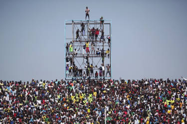 Fans climb a scoreboard to watch an African Cup of Nations qualifying soccer match between Ivory Coast and Democratic Republic of Congo in Kinshasa October 11, 2014. REUTERS/Media Coulibaly (DEMOCRATIC REPUBLIC OF CONGO - Tags: SPORT SOCCER) - RTR49TEO