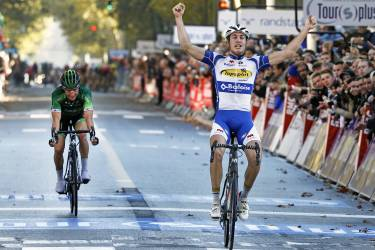 Belgium's Jelle Wallays raises his arms in victory as he crosses the finish line to win the Paris-Tours classic cycling race, in Tours, western France, Sunday, Oct. 12, 2014. France's Thomas Voeckler, left, finished second place. (AP Photo/Remy de la Mauviniere)