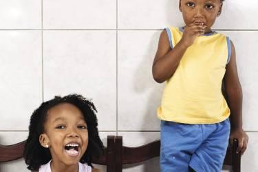 """3. Aricia Domenica Ferreira, 4 ans, et Hakim Jorge Ferreira Gomes, 2 ans, São Paulo.Au menu, jambon, fromage et pain beurré. Le biberon rose d'Aricia contient du chocolat au lait, celui de son frère Hakim...  du café au lait. Tradition culturelle, beaucoup de parents brésiliens donnent du café à leurs enfants, convaincus qu'il leur fournit  des vitamines et des antioxydants et les aide à se concentrer à l'école. Le père d'Hakim, Reginaldo Aguiar Gomes,  le trouve """"plus excité après"""". Le pédiatre de la famille dit qu'en boire avec modération ne fait pas de mal. photos HANNAH WHITAKER"""