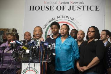 Rev. Al Sharpton speaks alongside Gwen Carr, mother of Eric Garner, left, Esaw Garner, Garner's wife, center right, and Emerald Garner, Garner's daughter, second from right, at the National Action Network headquarters in New York on Wednesday, Dec. 3, 2014 after a grand jury's decision not to indict a New York police officer involved in the death of Eric Garner. A video shot by an onlooker and widely viewed on the Internet showed the 43-year-old Garner telling a group of police officers to leave him alone as they tried to arrest him. The city medical examiner ruled Garner's death a homicide and found that a chokehold contributed to it. (AP Photo/John Minchillo)