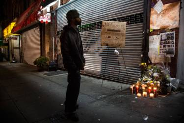 NEW YORK, NY - DECEMBER 03: A man pauses at an makeshift memorial for Eric Garner, the man killed by a police officer in July using a chokehold, outside the beauty salon where the confrontation took place on December 3, 2014 in the Staten Island borough of New York City. A grand jury declined to indict New York City Police Officer Daniel Pantaleo in Garner's death.   Andrew Burton/Getty Images/AFP == FOR NEWSPAPERS, INTERNET, TELCOS & TELEVISION USE ONLY ==